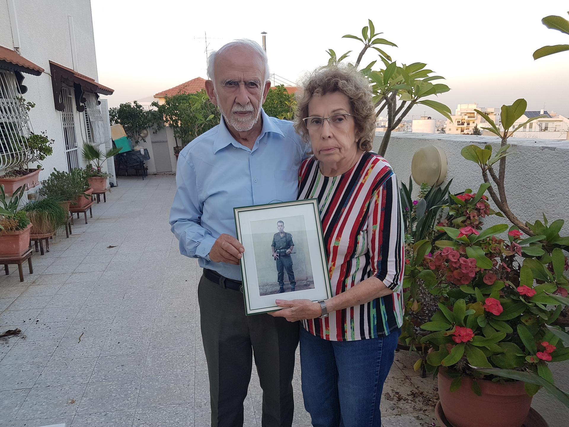"""שמואל ורינה חזון עם תמונה של בנם ניב ז""""ל. צילום: אייל עצמון"""