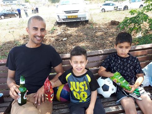 גיל מליחי, מאוהדי הליגה, עם שני ילדיו שמחונכים מגיל צעיר לאהבת הכדורגל. צילום: אבישי גמליאל